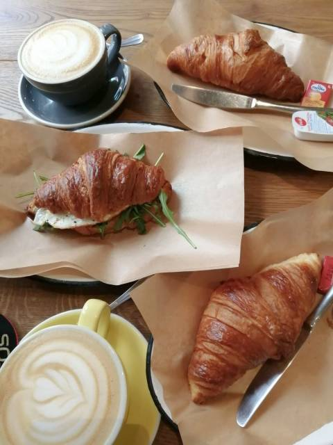 Desayuno de estilo francés en cafetería moderna de Budapest.