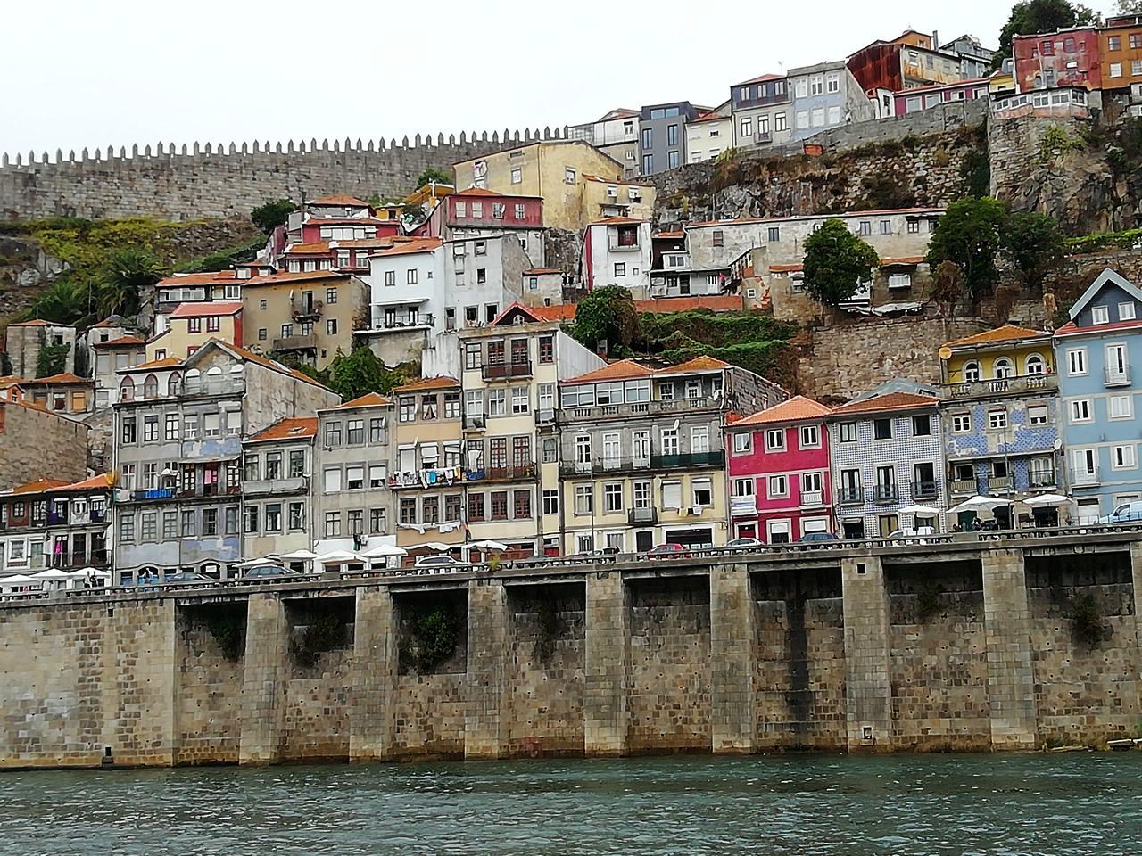 Casas con fachadas de colores y la muralla fernandina de Oporto al fondo.