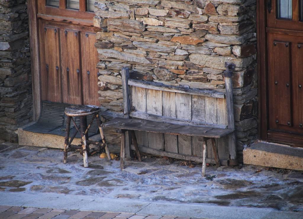 Bancos y taburetes muy rústicos de madera en una calle cualquiera de La Hiruela.