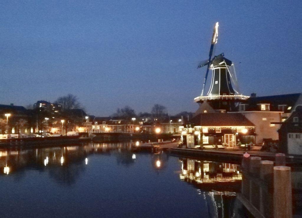 El molino de viento de Adriaan iluminado por la noche en la ciudad de Haarlem.